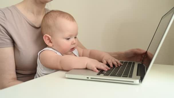 Detailní portrét malý chlapeček legrační výraz obličeje sedí na matčině klíně studuje notebook. Mladá máma pracuje z domova s počítačem. Domácí kancelář, rodičovství. Vzdálená práce, distanční vzdělávání. .