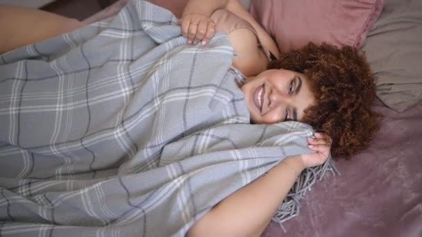 Krásné křivky plus velikost africké černošky afro vlasy ležící na posteli s šedou kostkovanou přikrývkou útulné ložnice design interiéru. Tělesná nedokonalost, tělesné přijetí, tělesná pozitivita a rozmanitost koncepce