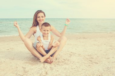 Mother and her son doing yoga on coast of sea on beach.