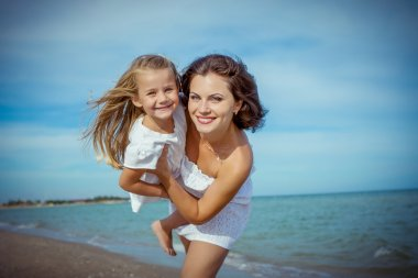 Happy beautiful mother and daughter enjoying beach time