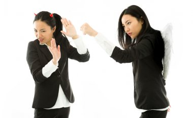 Angry white angel of a young Asian businesswoman punching the devil isolated on white background