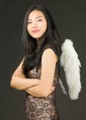 Side profile of a Asian young woman dressed up as an angel with her arms crossed