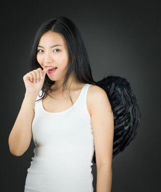 Asian young woman dressed up as an angel finger in mouth