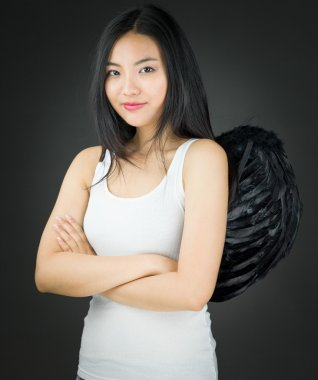 Confident Asian young woman dressed up as an angel with her arms crossed