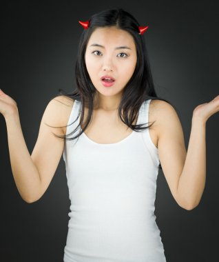 Asian young woman in devil horns dont know what to do