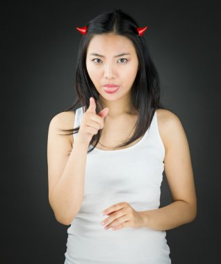 Asian young woman in devil horns sticking out her tongue with pointing