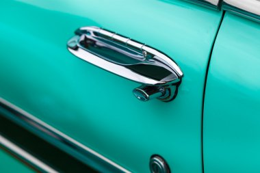 Car handle of a turquoise classic vintage car