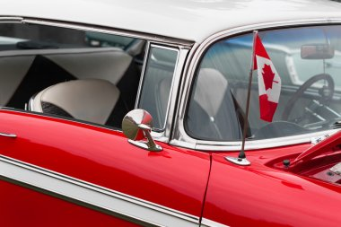 Canadian flag on bonnet of a red car