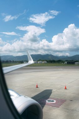 Airplane at airport with mountain range in background