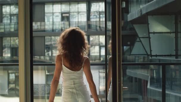 Na balkóně svého bytu jde mladá krásná žena. Užívá si počasí. 4K