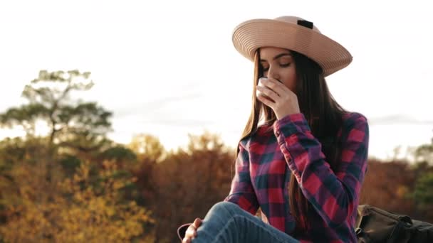 Egy fiatal nő forró teát iszik. Egy sziklán ül. Nézi a naplementét. Túrázás a hegyekben. 4K