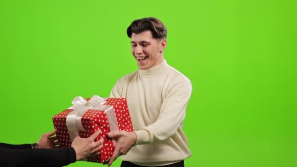 The man is standing and looking at the camera. He is given a gift and he is happy. He is standing on a green background. Green screen. 4K