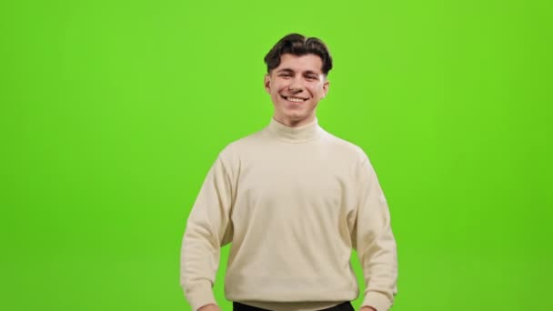 The man is standing and looking at the camera. He is raising his hands and showing a heart. He is smiling. He is standing on a green background. Green screen. 4K