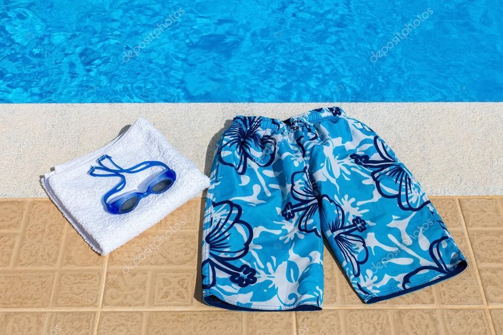 8fd7209ab0 Óculos azul calção de banho e toalha de banho na piscina — Foto de  benschonewille