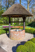 Photo New waterwell with bucket in park
