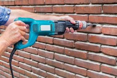 Arms holding drilling machine against brick wall