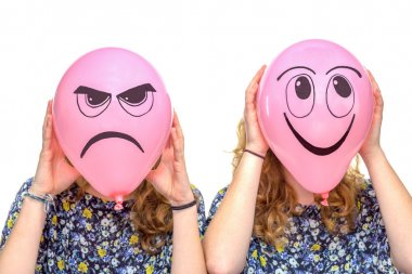 Two girls holding pink balloons with facial expressions