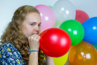 Teenage girl blowing inflating colored balloons