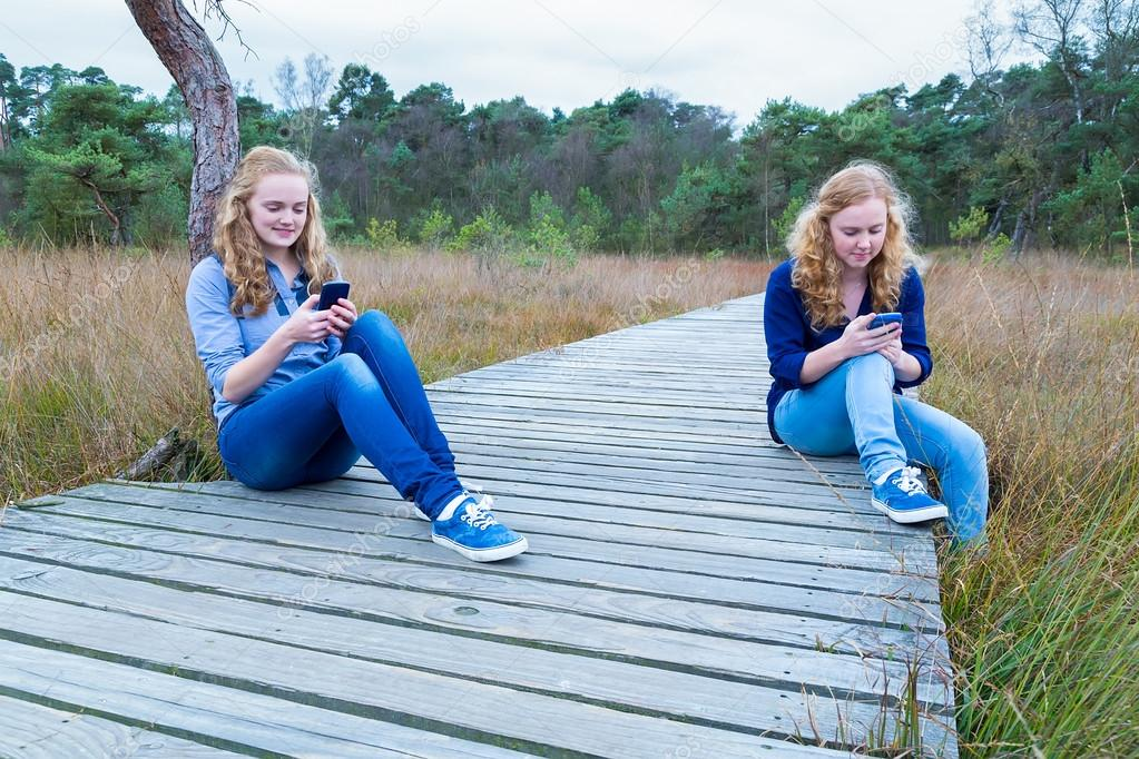 Two girls operating mobile phones in nature