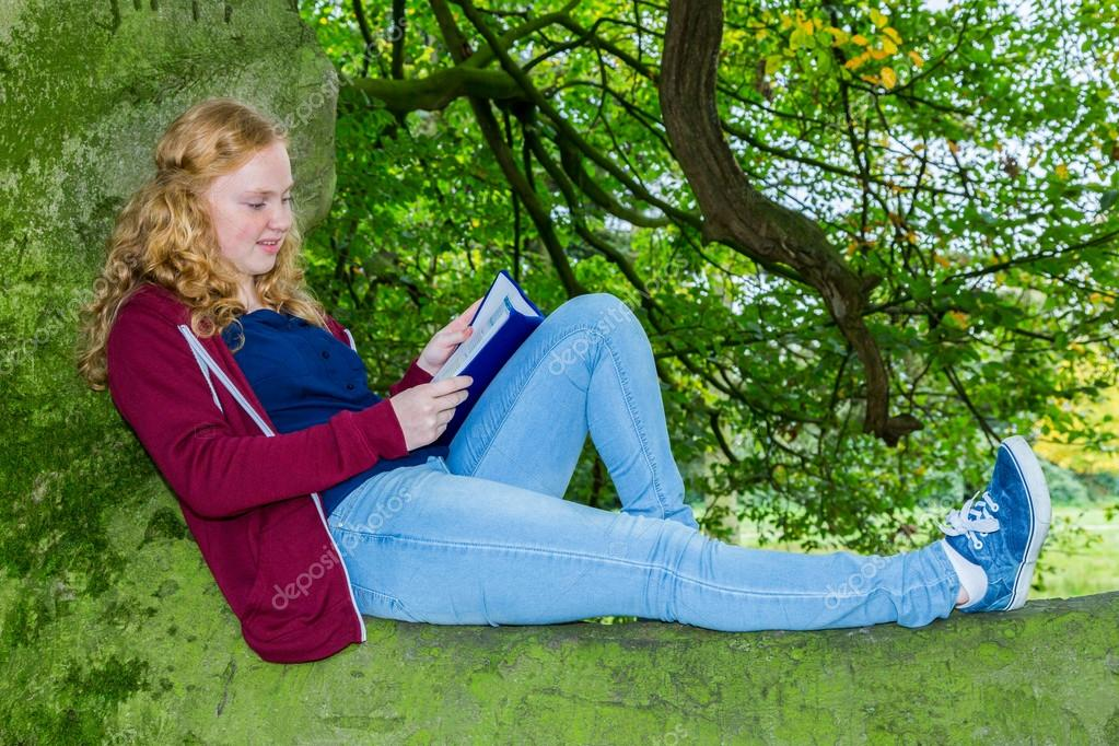 Dutch girl lying reading book in green tree