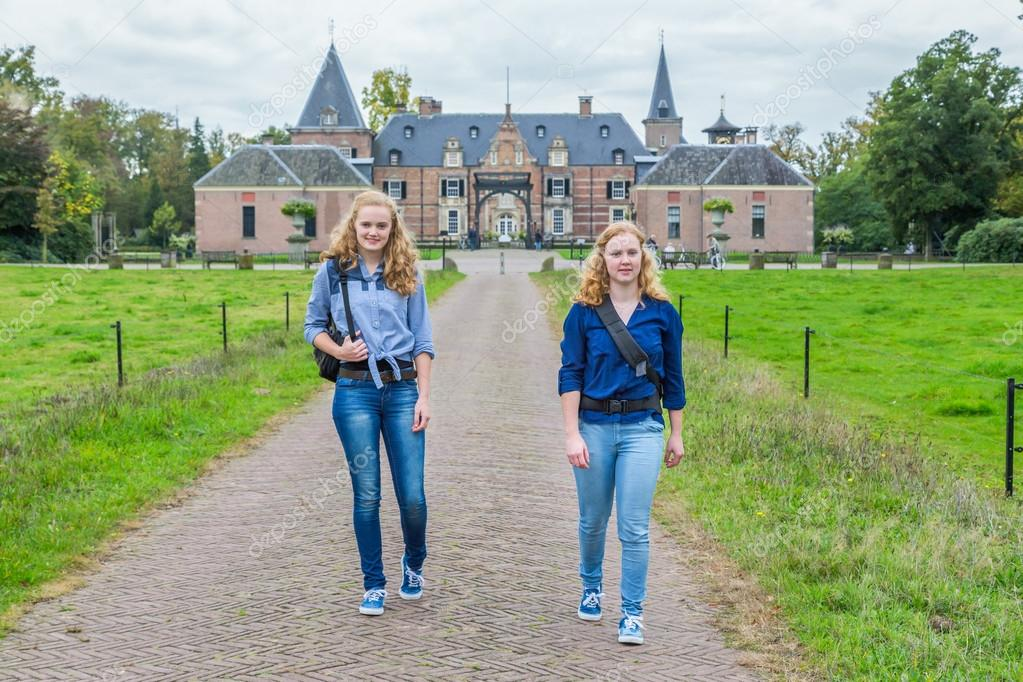 Two girls walking away from castle