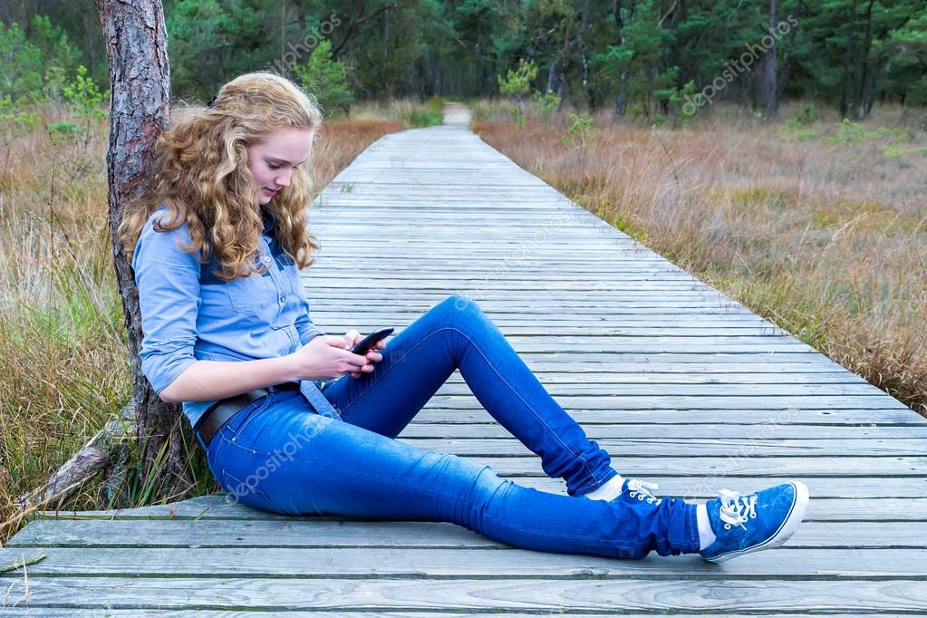 Girl sitting on wooden path in nature phoning mobile