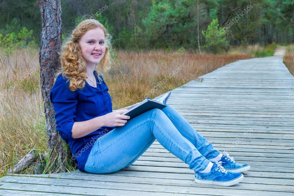 Dutch girl reading book on wooden path in forest