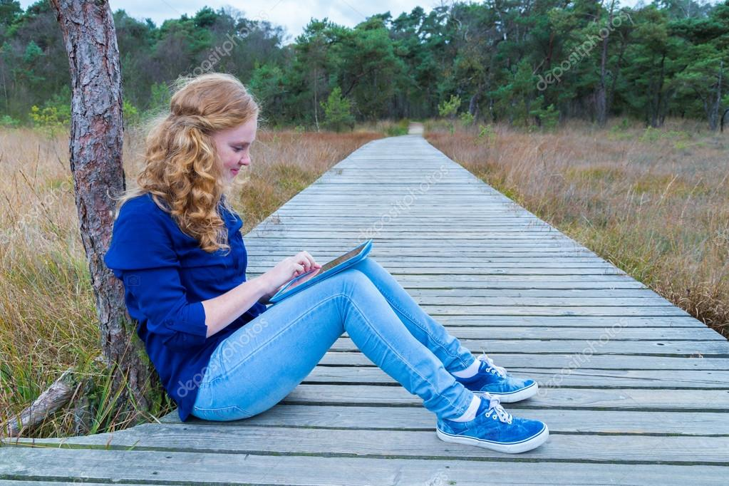 Dutch girl working with tablet computer on path in nature