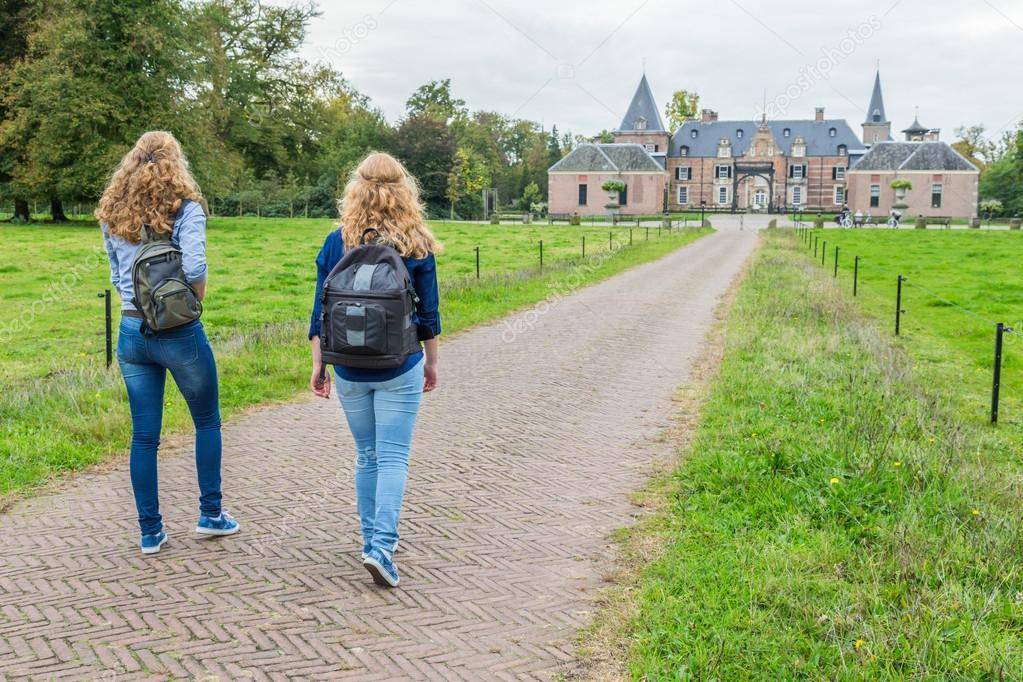 Two girls walking on road leading to castle