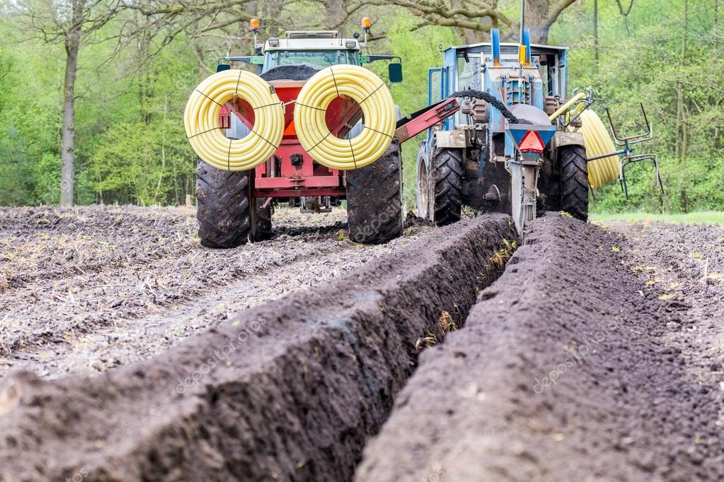 Two agriculture tractors putting drainage pipes in ground