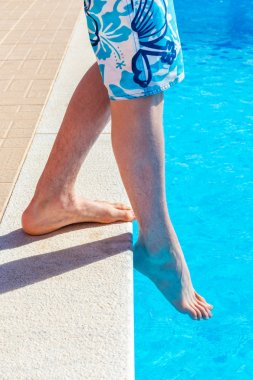 Legs with foot feeling water temparature in swimming pool