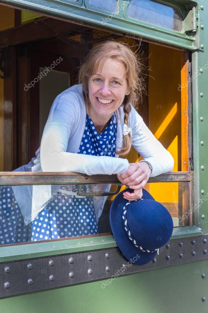 Dutch woman in old-fashioned clothes holding hat in train window