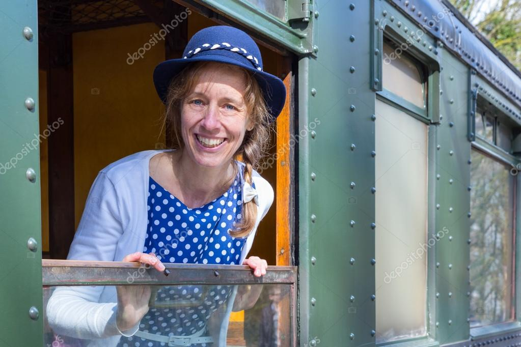 Dutch woman in old-fashioned clothes in window of steam train