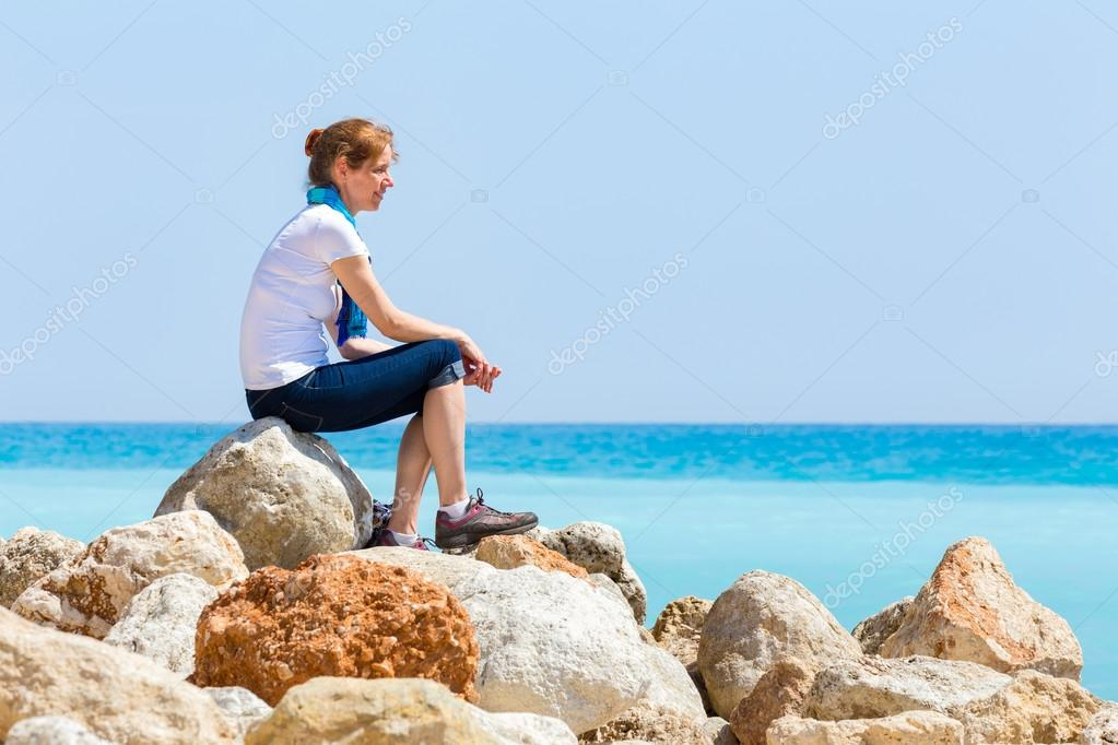 dutch woman sitting on rocks with blue sea horizon ストック写真