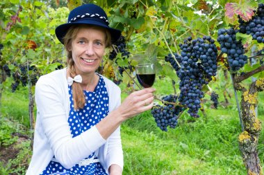 Caucasian woman toasting with glass of wine near bunches of blue