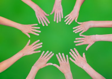 Five children hands joining in circle above green background