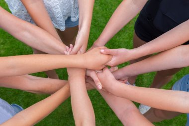 Many arms of children holding hands together