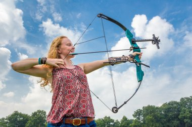 Young woman shooting archery with compound bow and arrow