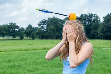 Teenage girl feeling fearful with apple and arrow on head
