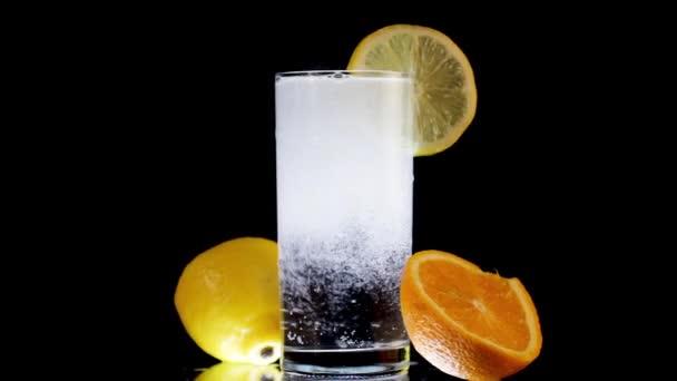 Sprudelndes Sodawasser mit Zitrone und Orange. Erfrischendes Getränk auf schwarzem Hintergrund