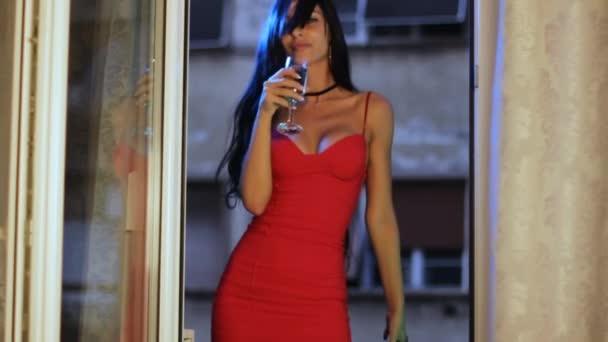 Sexy žena v červených šatech pijící víno, smyslně se pohybuje na balkóně hotelového pokoje.