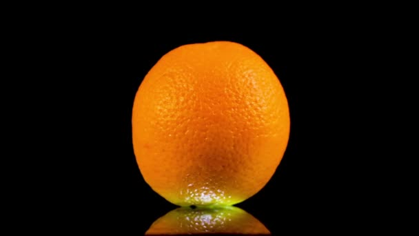Close Up of Spinning Orange. Fruit on Black Background