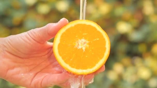 Orange in hand under flowing water