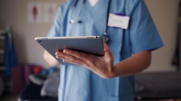 Nahaufnahme einer Physiotherapeutin in Uniform und Stethoskop, die Patientenbericht auf digitalem Tablet liest