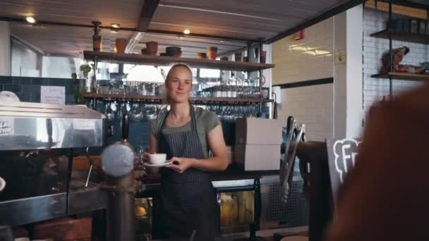 Mosolygó szőke kávézó női tulajdonos átad egy kávéscsészét egy ügyfélnek