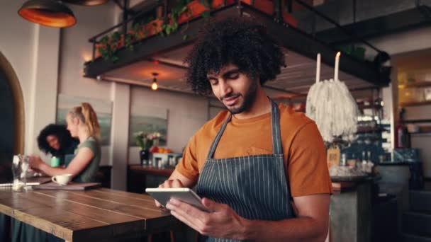 Handsome young male barista using tablet as personal organizer to add new orders at coffee shop