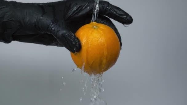 Washing the orange with water splash on grey background, slow motion. Man hand in black glove hold orange and wash it under water stream