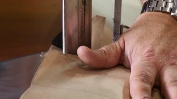 Elektrický šicí stroj krájí textil. Mužský dělník na šití používá elektrický řezací stroj.