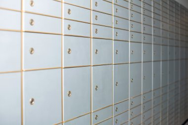 White closed lockers of various sizes on wall
