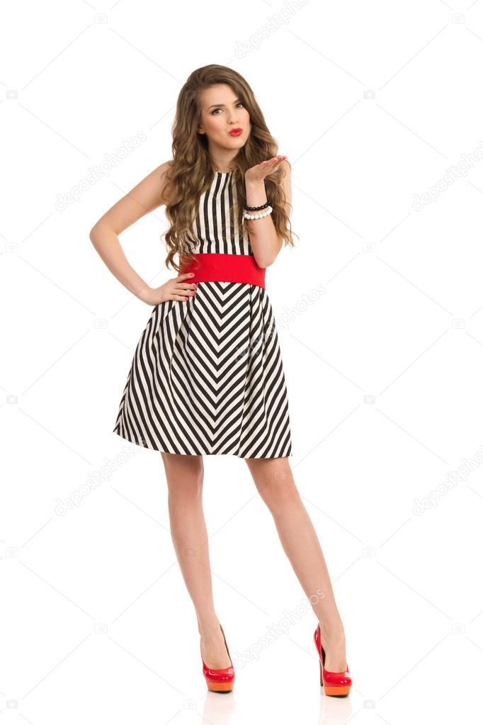 085470035 Elegante mujer con cabello largo castaño en vestido rayado blanco y negro  que sopla un beso